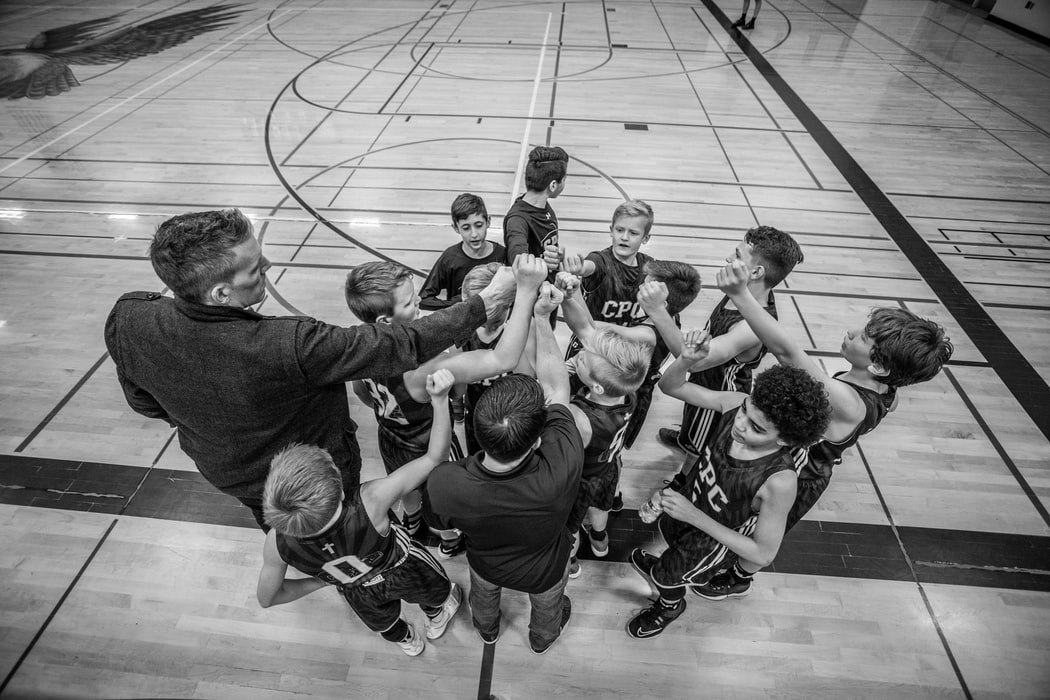 coach huddled with basketball team of kids
